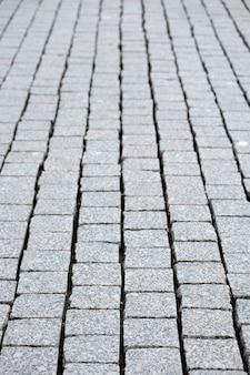 Strada pavimentata con primo piano di vista verticale di ciottoli grigi