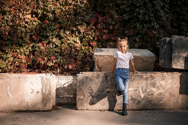 Foto di strada di una bella ragazza in jeans e maglietta bianca su uno sfondo di lastre di cemento e foglie autunnali