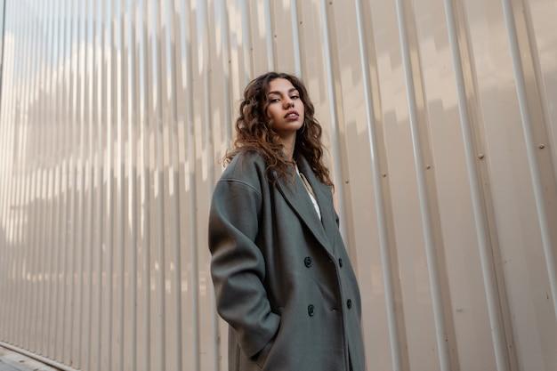 Il ritratto di strada di una bellissima giovane modella con i capelli ricci in un cappotto verde alla moda si trova vicino a una parete di metallo all'aperto