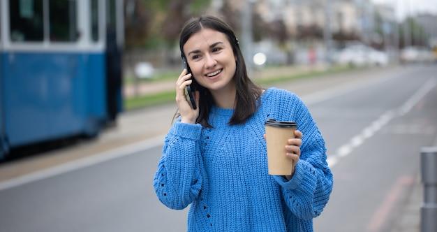 Ritratto di strada di una giovane donna allegra che parla al telefono con il caffè alla mano su sfondo sfocato.