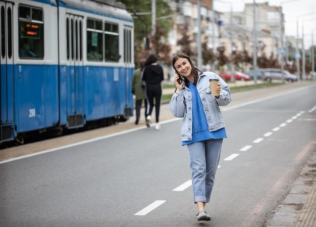 Ritratto di strada di una giovane donna allegra che parla al telefono con il caffè in mano