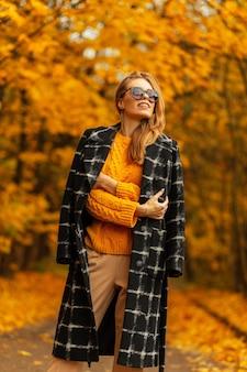 Ritratto di strada splendida bella giovane donna in occhiali da sole alla moda in cappello di paglia in elegante abito a righe della nuova collezione estiva contro il cielo durante il fine settimana di sole. ragazza con labbra sexy in posa in città.