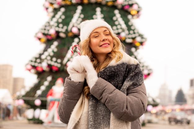 Ritratto di strada sorridente bella giovane donna sulla festa di natale festivo. ragazza che indossa guanti invernali alla moda lavorati a maglia e azienda lolipop.