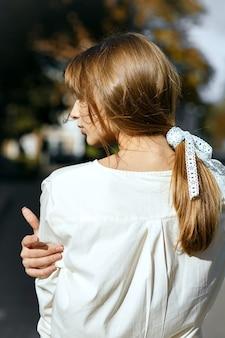 Colpo di strada di una bellissima modella bruna con un nastro nei capelli