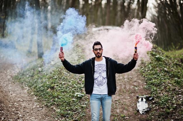 L'uomo arabo di stile di strada in occhiali tiene il chiarore della mano con la bomba della granata fumogena rossa e blu.