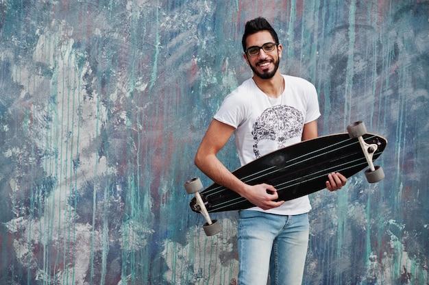 Uomo arabo street style in occhiali con longboard in posa contro il muro colorato, come se suonasse la chitarra.