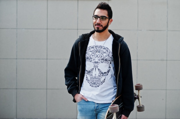 L'uomo arabo dello stile della via in occhiali con il longboard ha proposto contro la parete grigia.