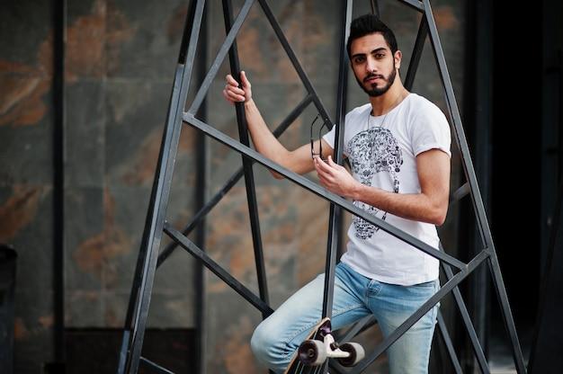 Uomo arabo street style in occhiali con longboard poste all'interno della costruzione della piramide di metallo.