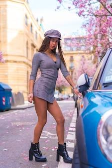 Street style in città, bruna ragazza caucasica in una giacca di pelle e un berretto, salendo nella sua auto blu in città con gli alberi fioriti in primavera, foto verticale