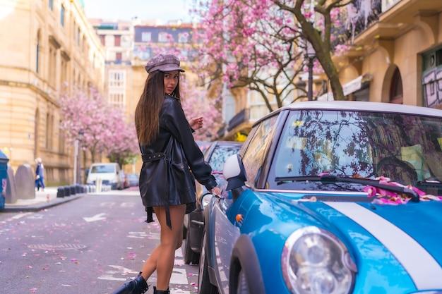 Street style in città, bruna ragazza caucasica in una giacca di pelle e un berretto, salendo nella sua auto blu in città con gli alberi in fiore in primavera