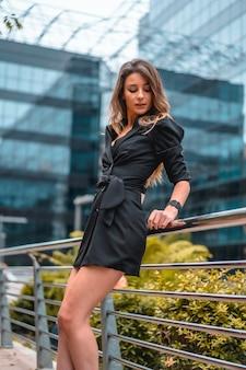Street style, una giovane donna caucasica bionda intraprendente in un abito nero nell'edificio di vetro nero dove lavora in background. appoggiato a un burrone