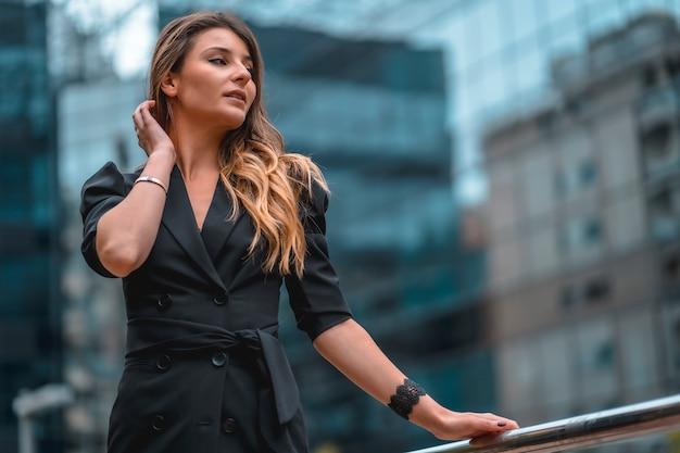 Street style, una giovane donna caucasica bionda intraprendente in un abito nero nell'edificio di vetro nero dove lavora in background. guardando a destra e accarezzandole i capelli