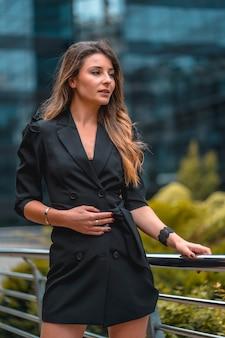 Street style, una giovane donna caucasica bionda intraprendente in un abito nero nell'edificio di vetro nero dove lavora in background. una mattina di primavera appoggiata a una ringhiera