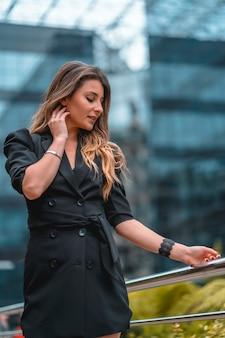 Street style, una giovane donna caucasica bionda intraprendente in un abito nero nell'edificio di vetro nero dove lavora in background. una mattina di primavera