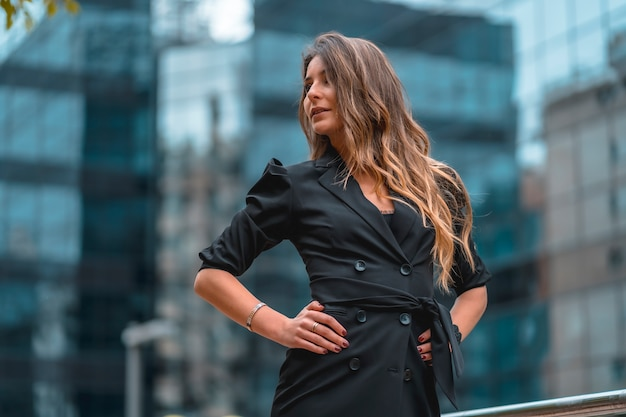 Street style, una giovane donna caucasica bionda intraprendente in un abito nero nell'edificio di vetro nero dove lavora in background.