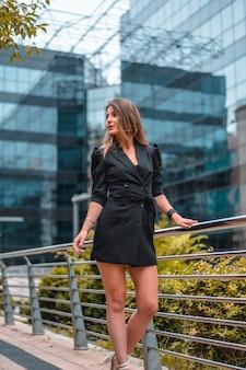 Street style, un'intraprendente giovane donna caucasica bionda in uno splendido abito nero corto, nell'edificio di vetro nero dove lavora in background. appoggiato a una ringhiera