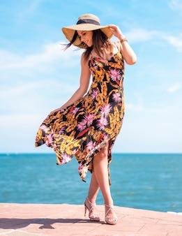 Street style, una giovane bruna con un abito floreale, un cappello di paglia e tacchi. abito mosso dal vento con il mare