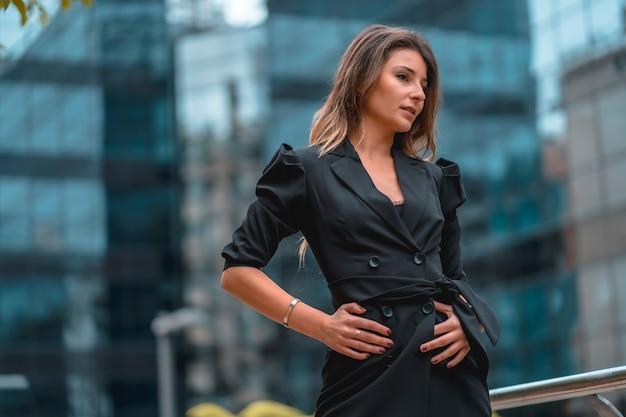 Street style, una giovane imprenditrice bionda caucasica nell'edificio di vetro nero dove lavora in background.