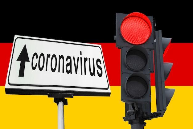 Semaforo stradale con segnale di divieto acceso. sullo sfondo della bandiera della germania. divieto di ingresso