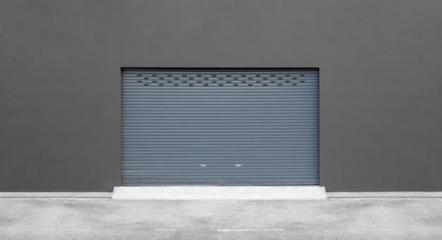 Sfondo muro di strada. porta avvolgibile e pavimento in cemento all'esterno dell'edificio industriale per uso industriale