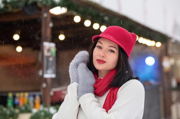 Il ritratto invernale di strada di un'adorabile giovane donna indossa un berretto lavorato a maglia e una sciarpa in posa in caso di nevicata. spazio vuoto