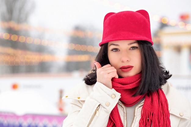 Il ritratto invernale di strada di una giovane donna seducente indossa un berretto rosso e una sciarpa lavorata a maglia in posa in caso di nevicata. spazio per il testo