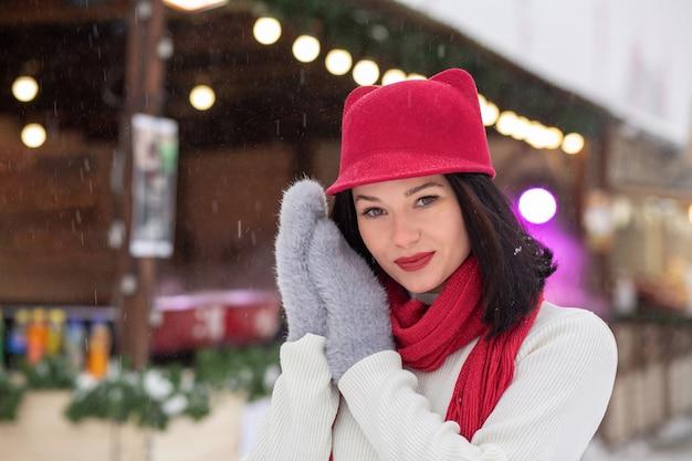Ritratto di strada invernale di una favolosa giovane donna che indossa un berretto rosso e una sciarpa lavorata a maglia in posa in caso di nevicata. spazio per il testo