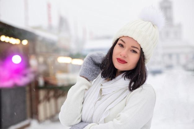 Il ritratto invernale di strada di una giovane donna alla moda indossa berretto lavorato a maglia e sciarpa in posa in caso di nevicata. spazio vuoto
