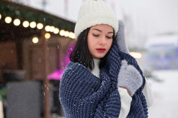Il ritratto invernale di strada di una giovane donna alla moda indossa un berretto e una sciarpa lavorati a maglia in posa di neve