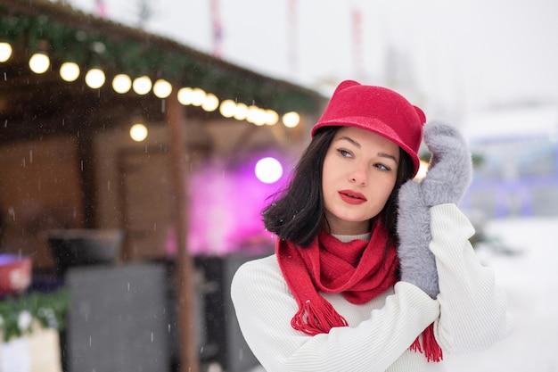 Il ritratto invernale di strada di una meravigliosa giovane donna indossa un berretto lavorato a maglia e una sciarpa in posa in caso di nevicata. spazio vuoto