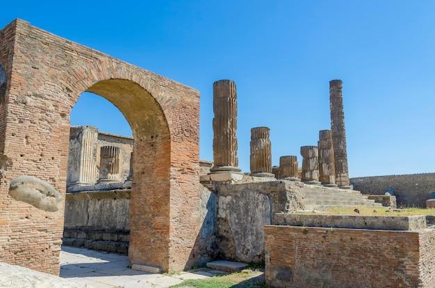 Strada con arco e resti di colonne a pompei