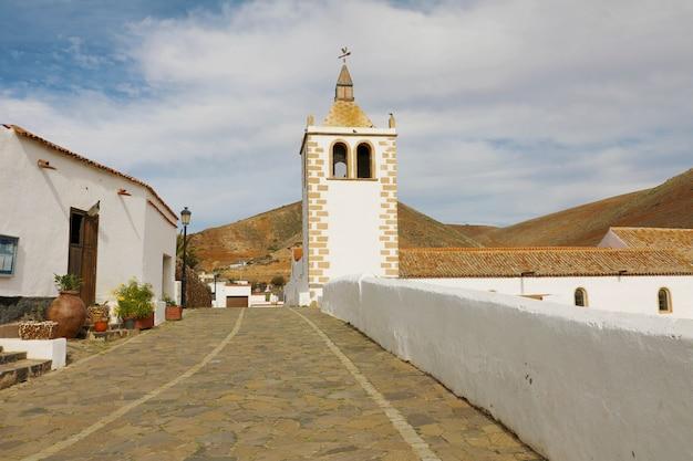 Strada con il campanile della chiesa di santa maria de betancuria nel villaggio di betancuria a fuerteventura, spagna