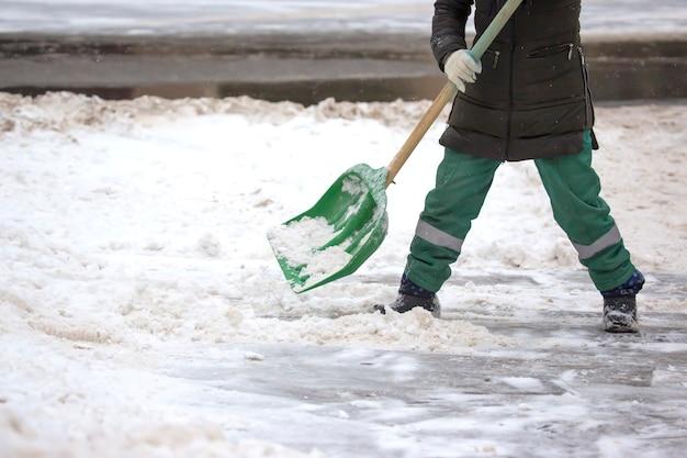 L'operatore di strada spala la neve dal marciapiede