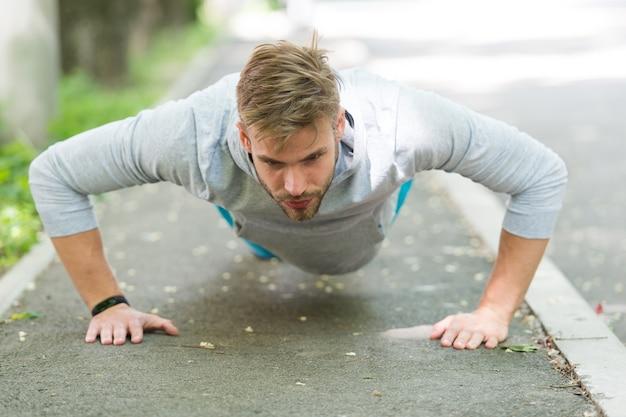 Forza e motivazione. uomo in abiti sportivi che fa flessioni all'aperto. allenamento motivato ragazzo nel parco. lo sportivo migliora la sua forza con l'esercizio push up. l'uomo ha la motivazione per il successo sportivo.