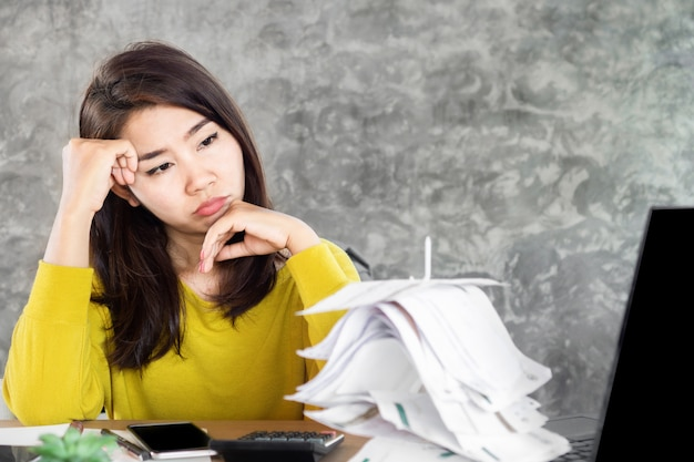 Donna asiatica di sforzo che esamina le fatture finanziarie non pagate