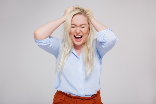 Concetto di stress e depressione - ritratto di infelice bella donna bionda taglie forti che urla su sfondo grigio con spazio copia
