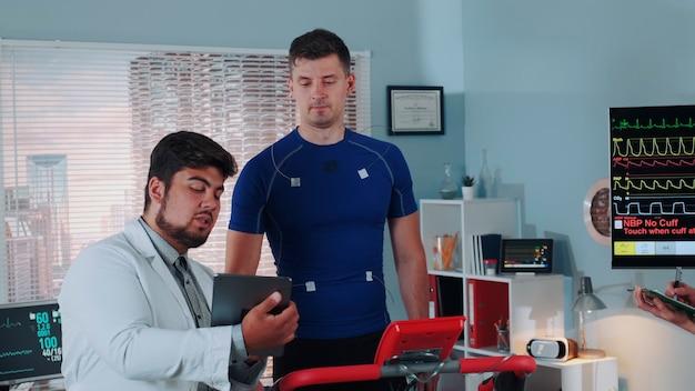 Test da sforzo nel medico di laboratorio sportivo con tablet che spiega i dati ekg degli atleti