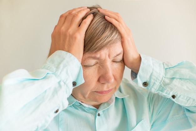 Anziano della donna di sforzo. salute mentale. urla di depressione, mal di testa, attacchi di panico, violenza, emicrania, salute psicologica