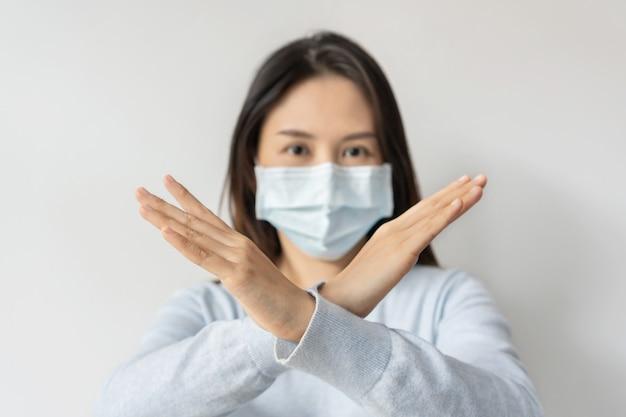 Sottolinea la giovane donna asiatica che indossa una maschera medica che fa il segno x con le mani incrociate, indicando di fermarsi o dire no su sfondo bianco. copia spazio