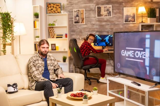 Giocatore maschio stressato e arrabbiato che perde una partita mentre gioca a tarda notte in soggiorno