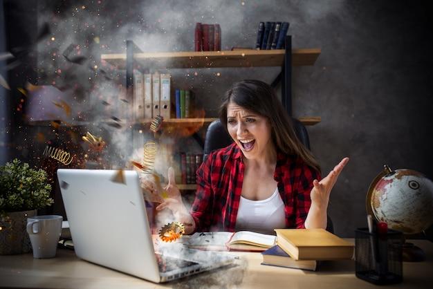 Donna stressata e arrabbiata con computer esploso a causa di superlavoro