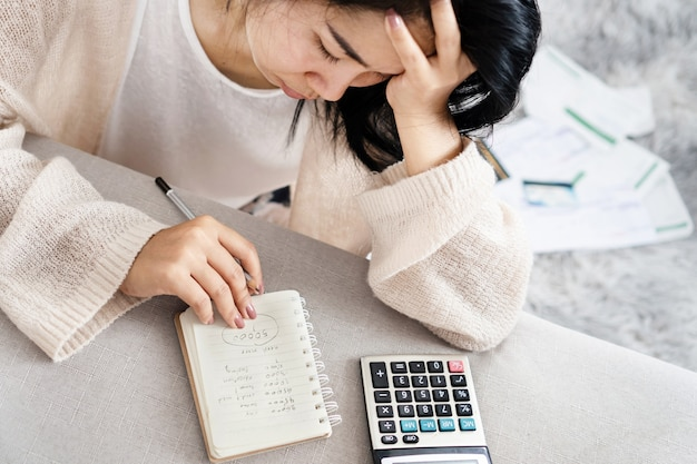 Donna asiatica stressata che calcola il suo debito guardando l'elenco delle spese sul blocco note