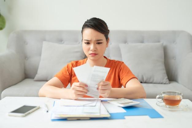 Mano di donna asiatica stressata che tiene fatture finanziarie non pagate