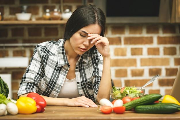 Bella giovane donna sollecitata in cucina. stanco a casa.