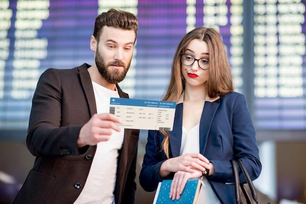 Coppia d'affari stressata che guarda la carta d'imbarco controllando l'orario di partenza davanti all'orario dell'aereo in aeroporto