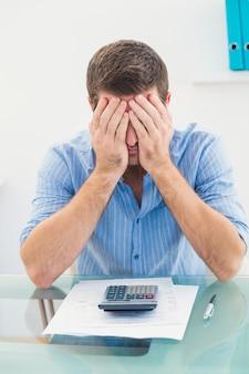 Stressato uomo d'affari che copre il viso alla sua scrivania