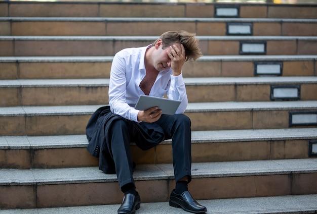 Sottolineato imprenditore seduto sulla scala