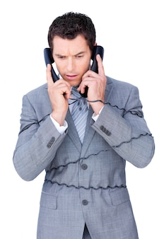 L'uomo d'affari sollecitato si aggroviglia in su nei cavi del telefono