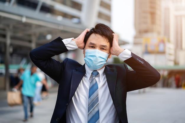 Uomo d'affari stressato con mascherina medica durante una pandemia di coronavirus in città