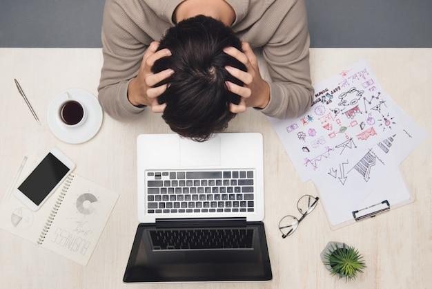 Uomo d'affari stressato che lavora alla scrivania sul posto di lavoro